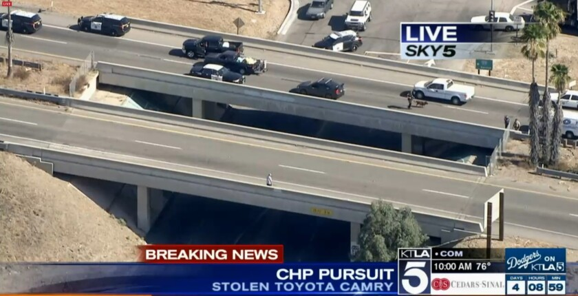 A suspected car thief stands at the edge of a 15 Freeway overpass.