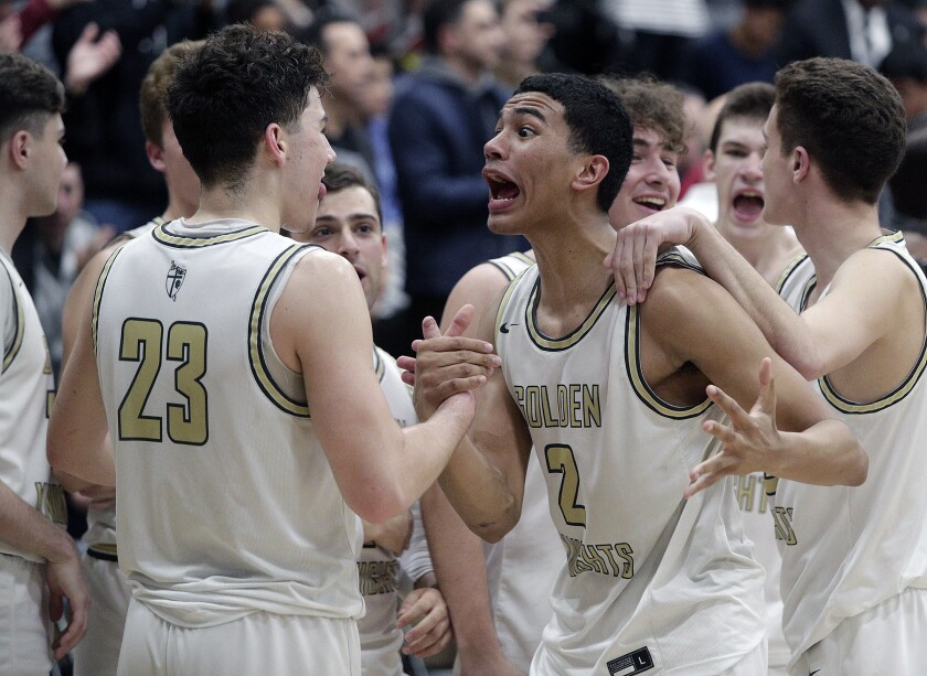 St. Francis' Andre Henry (2) greets teammates after a victory over Eastvale Roosevelt in the Southern California Regional Division II final in what turned out to be his final high school game after the cancellation of the state basketball championships.