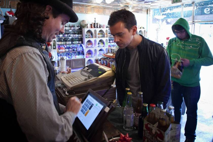 Square founder Jack Dorsey, right, makes a purchase in December at the Fizzary in San Francisco. The business uses his company's mobile payment technology with an iPad.