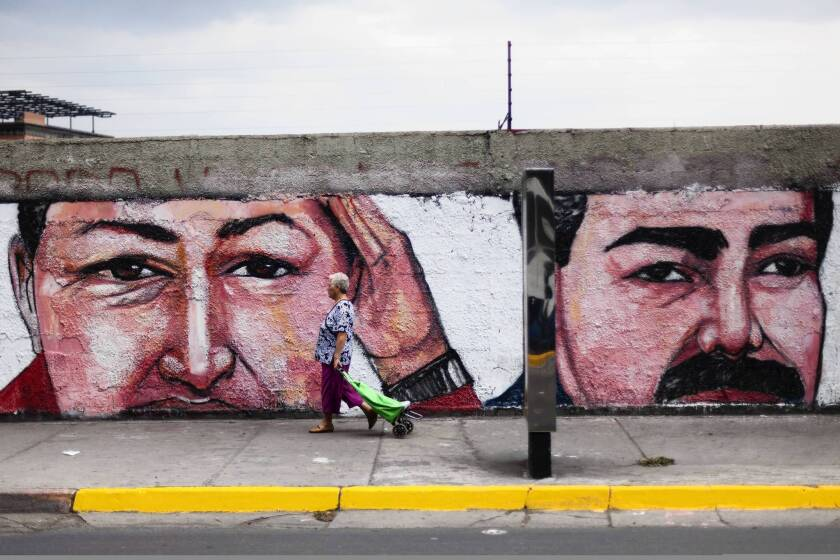 A mural in Caracas depicts late Venezuelan President Hugo Chavez, left, and his anointed successor, new President Nicolas Maduro.