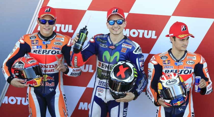 From left:  Jorge Lorenzo, Marc Marquez and Dani Pedrosa pose together during the qualifying session for Sunday's Valencia Motorcycle Grand Prix, the last race of the season, at the Ricardo Tormo circuit in Cheste near Valencia, Spain, Saturday Nov. 7, 2015. (AP Photo/ Eduardo Manzana)