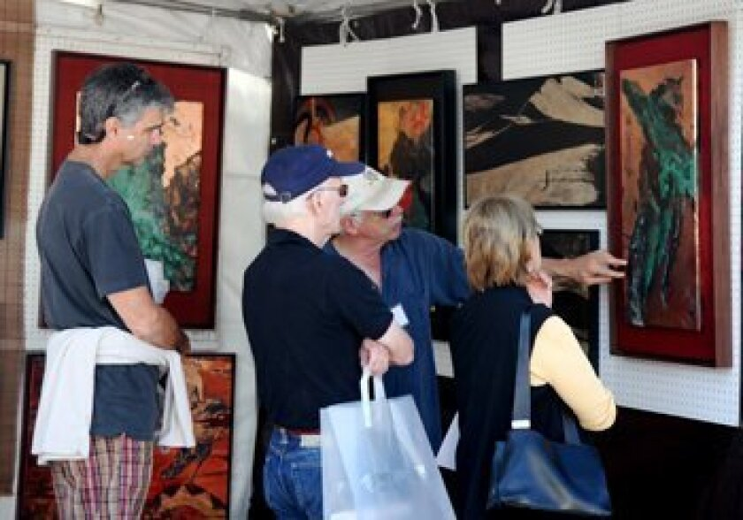 Festival goers check out art at the 2010 event. Light file photo