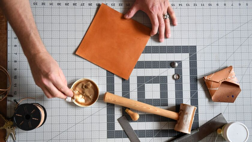 Peter Maxwell treats a piece of leather at his flagship store Made Solid in Hollywood.