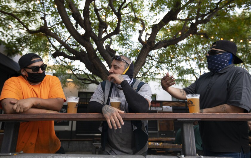 Three men enjoy a beer outside Grand Central Market in Los Angeles.