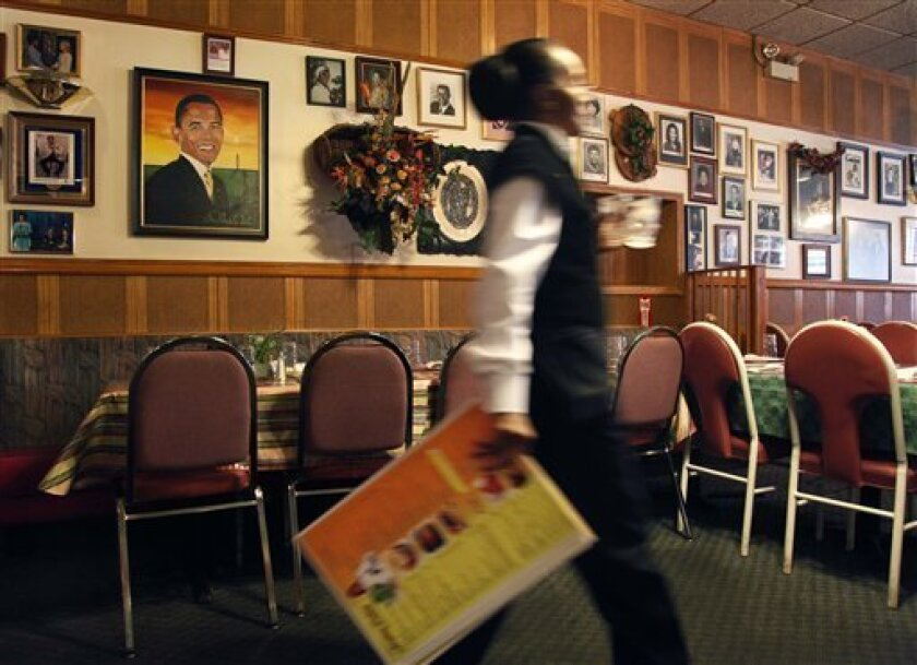 In this photo taken Tuesday, Aug. 16, 2011a portrait of Presidet Obama anchors a wall of African-America art and portraits of local and national celebrities who have eaten at Hard Time Josephine's Cooking soul food restaurant, in the Chatham neighborhood of in Chicago. Over the past 10 years as Chicago has lost more than 17 percent of its black population, one soul food place after another has closed and the surviving few like Josephine's are struggling. (AP Photo/Charles Rex Arbogast)