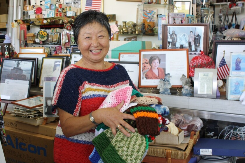 Miki Sessler displays beanies in her Huntington Beach store, Miki's California Yarn Sales. The beanies are shipped to servicemen and women to show they are supported.