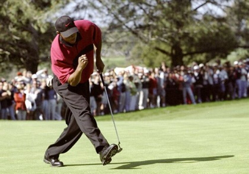 Tiger Woods cheers as he sinks a putt in the final round of the Buick Invitational at Torrey Pines in 1999.
