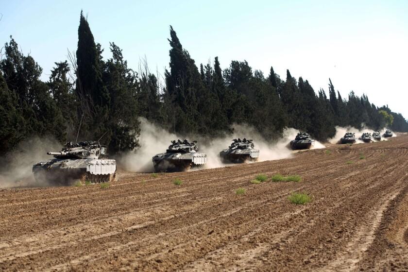 A convoy of Israeli Merkava tanks roll near Israel's border.