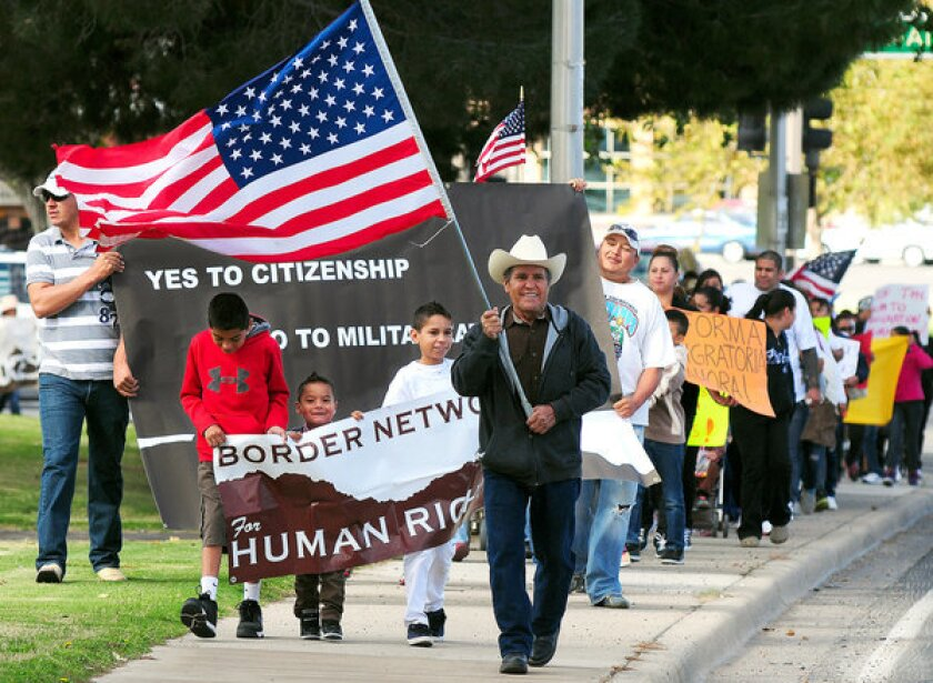 Jose Gonzalez of El Paso carries the American flag as he leads demonstrators to the office of Rep. Steve Pearce (R-N.M.) earlier this year.