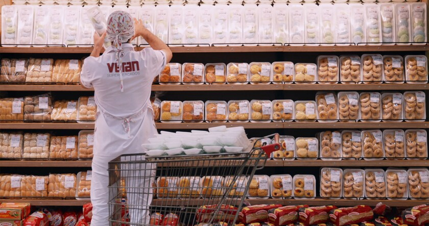 "A worker stocks baked goods in the documentary ""My Darling Supermarket."""