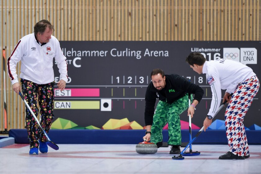 Norway's Crown Prince Haakon pushes the first curling stone with Pal Trulsen, 2002 Curling Olympic gold medalist, left, and Thomas Ulsrud, Men's Norway curling captain at The Kristins Hall, ahead of the Winter Youth Olympic Games, Lillehammer, Norway, Friday Feb. 12, 2016. (Thomas Lovelock/IOC via