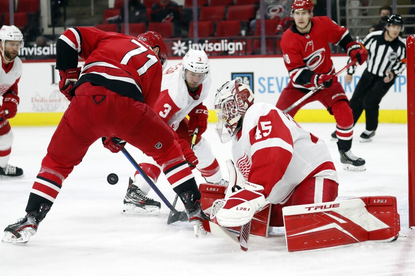 Carolina Hurricanes' Jesper Fast (71) tries to gather in the puck in front of Detroit Red Wings goaltender Jonathan Bernier (45) and Alex Biega (3) during the second period of an NHL hockey game in Raleigh, N.C., Monday, April 12, 2021. (AP Photo/Karl B DeBlaker)