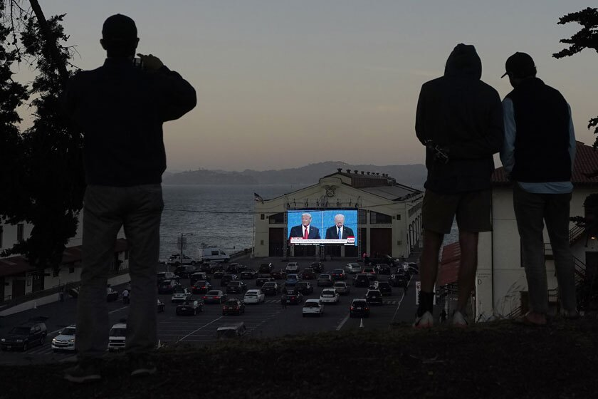 People watch a debate between President Trump and Joe Biden on an outdoor screen in San Francisco.