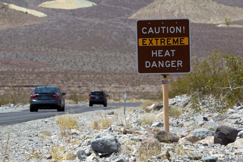 FILE PHOTO: A sign warns of extreme heat as tourists enter Death Valley National Park in California