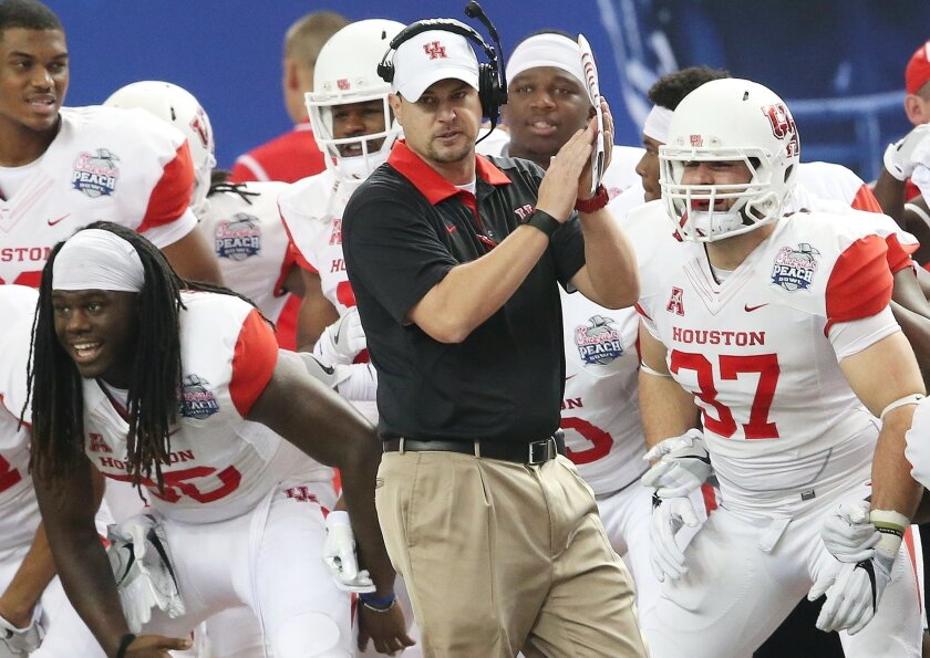 FILE - In this Dec. 31, 2015, file photo, Houston head coach Tom Herman watches play against Florida State during the first half of the Peach Bowl NCAA college football game in Atlanta. The AAC notched 10 wins in 2015 against Power Five conference teams, including Mississippi, Miami, Penn State and