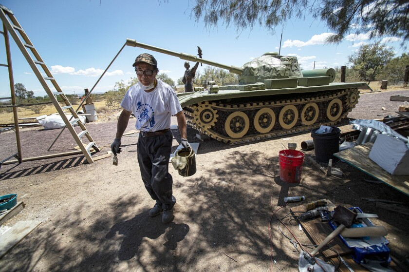 "Chen Weiming takes a break from sculpting a military tank replica as part of his life-size monument called ""Tank Man"" in remembrance of the 30th anniversary of the Tiananmen Square massacre in Newberry Springs, Calif."
