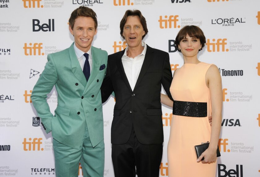"""Eddie Redmayne, from left, and James Marsh and Felicity Jones attend the premiere for """"The Theory of Everything"""" on day 4 of the Toronto International Film Festival at the TIFF Bell Lightbox on Sunday, Sept. 7, 2014, in Toronto. (Photo by Chris Pizzello/Invision/AP)"""