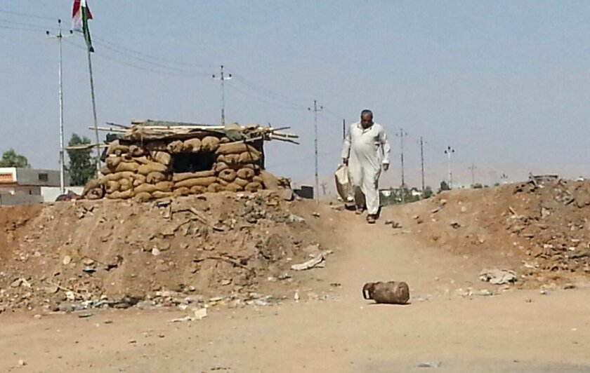 """FILE - In this Tuesday, July 8, 2014 file photo, an Iraqi refugee man who left his hometown of Mosul walks towards Irbil as he crosses a berm that separates Kurdish fighters and militants of the Islamic State group outside the northern city of Mosul, Iraq. An Iraqi military spokesman says the long-awaited military operation to recapture the northern city of Mosul from Islamic State militants """"has begun."""" The spokesman for the Joint Military Command, Brig. Gen. Yahya Rasool, says Iraqi forces retook several villages on the outskirts of the town of Makhmour, east of Mosul, on Thursday, March 24, 2016. (AP Photo, File)"""
