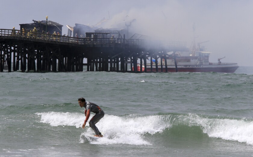 Firefighters mop up a blaze at the end of the Seal Beach Pier Friday morning as a surfer catches a wave.