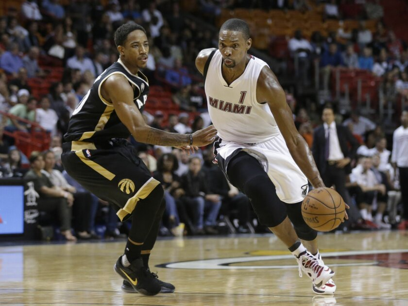FILE - In this Friday, Dec. 18, 2015 file photo, Miami Heat forward Chris Bosh (1) drives to the basket as Toronto Raptors guard DeMar DeRozan, left, defends during the second half of an NBA basketball game in Miami. (AP Photo/Lynne Sladky)