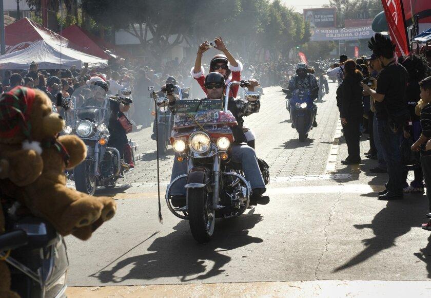 Motorcycle riders bearing Christmas gifts drive down Avenida Revolucion Sunday for the 28th Tijuana Toy Run.