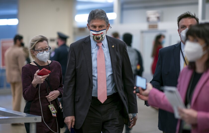 FILE - In this Feb. 25, 2021, file photo, reporters question Sen. Joe Manchin, D-W.Va., as he arrives for votes on President Joe Biden's cabinet nominees, at the Capitol in Washington. (AP Photo/J. Scott Applewhite, File)