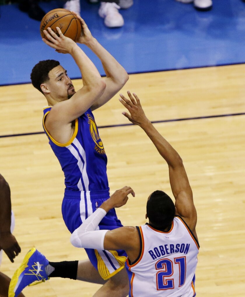 Golden State Warriors guard Klay Thompson (11) shoots over Oklahoma City Thunder guard Andre Roberson (21) during the first half in Game 6 of the NBA basketball Western Conference Finals in Oklahoma City, Saturday, May 28, 2016. (AP Photo/Alonzo Adams)