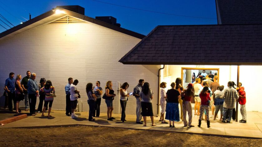 --FILE--People wait in line to vote at polling place located in a church in Phoenix in this Nov. 6,