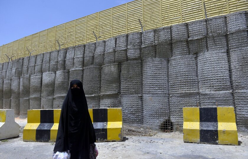A woman passes barriers around the closed German Embassy in Sana, the Yemeni capital. Authorities have beefed up security around diplomatic compounds and key government institutions during a worldwide terrorist alert issued by the U.S. State Department last week.