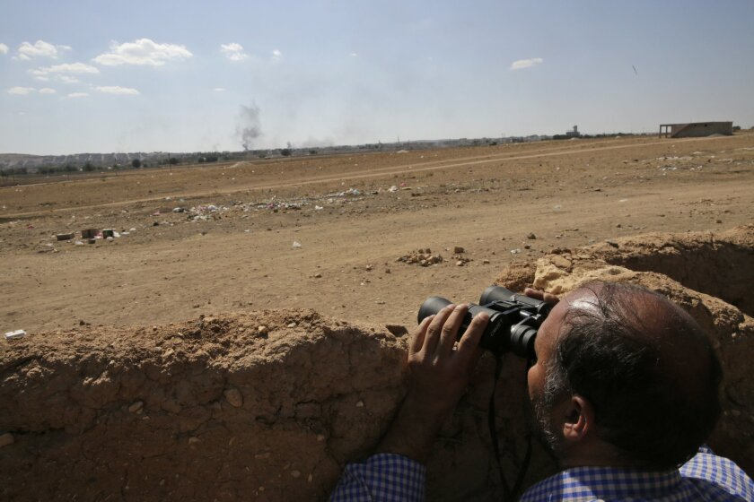 A Turkish Kurd uses binoculars in Mursitpinar, on the outskirts of Suruc, on the Turkey-Syria border, as he watches the intensified fighting between militants of the Islamic State group and Kurdish forces in Kobani, Syria, background, Wednesday, Oct. 8 Oct. 7, 2014. Kobani, also known as Ayn Arab and its surrounding areas have been under attack since mid-September, with militants capturing dozens of nearby Kurdish villages. (AP Photo/Lefteris Pitarakis)