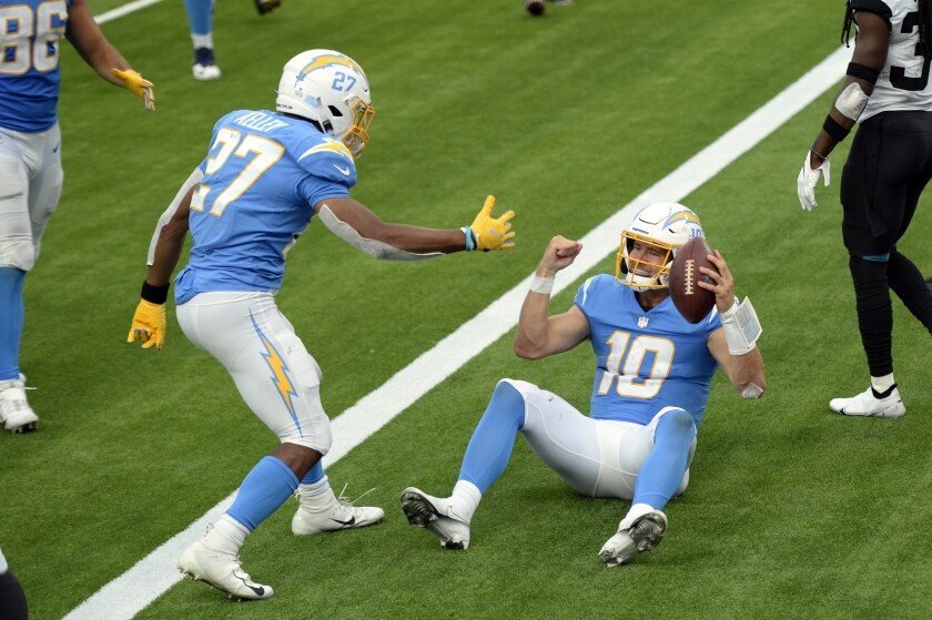 Los Angeles Chargers quarterback Justin Herbert (10) celebrates his rushing touchdown with Joshua Kelley (27) during the second half of an NFL football game against the Jacksonville Jaguars Sunday, Oct. 25, 2020, in Inglewood, Calif. (AP Photo/Kyusung Gong)