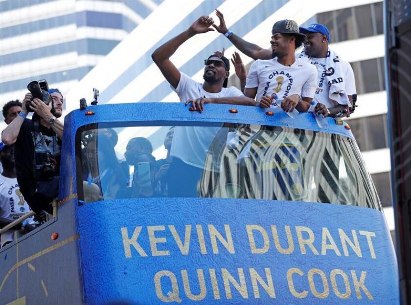 Los jugadores de los Golden State Warriors Kevin Durant (c) y Quinn Cook (2d) saludan a los aficionados durante el desfile de la victoria en honor a los recientes campeones de la NBA este martes 12 de junio de 2018, en el centro de Oakland (EE.UU.). EFE