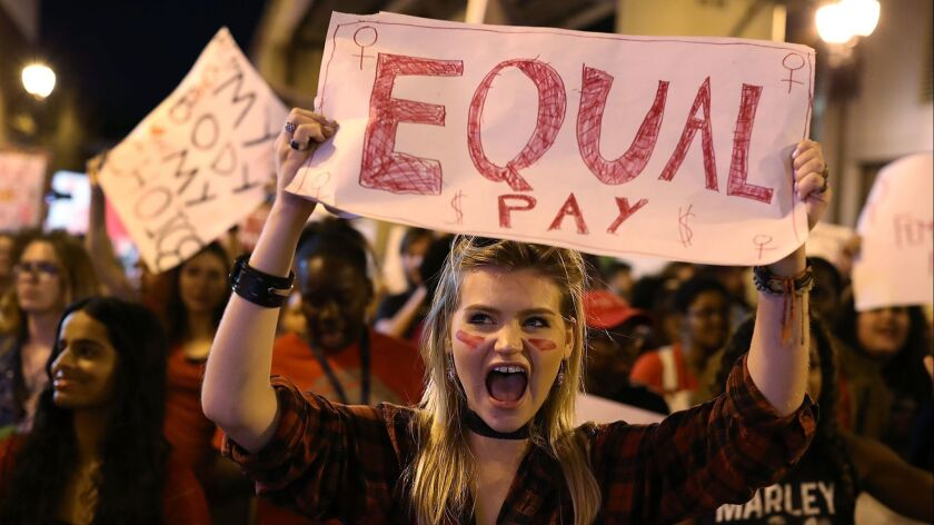An International Women's Day marcher lets her support of equal pay be known.