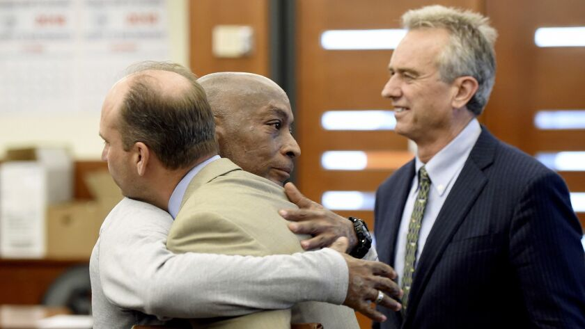 Dewayne Johnson, center, hugs one of his attorneys, next to lawyer and member of his legal team Robe