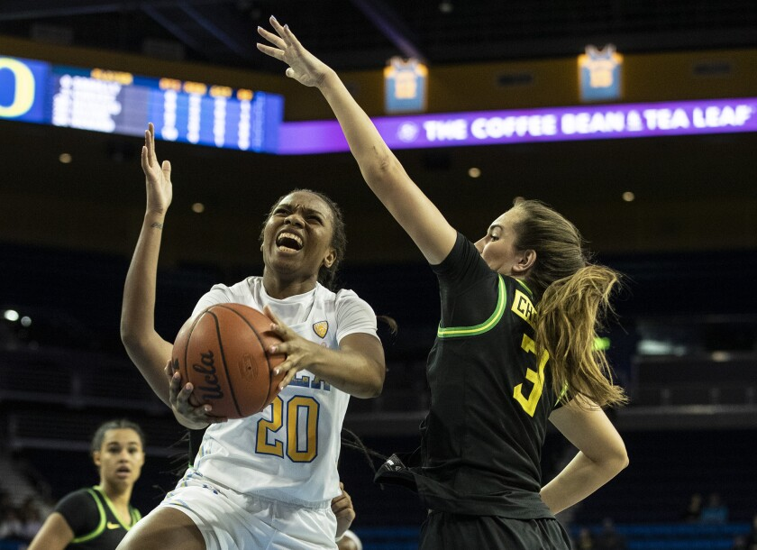 UCLA guard Charisma Osborne drives to the basket against Oregon guard Taylor Chavez during the first half of a game Feb. 14 at Pauley Pavilion.