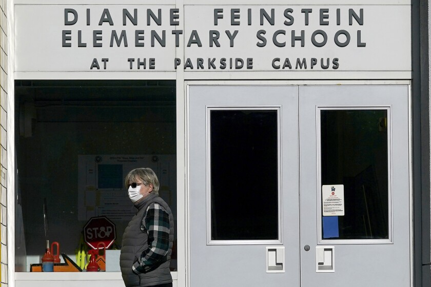 A pedestrian walks below a sign for Dianne Feinstein Elementary School