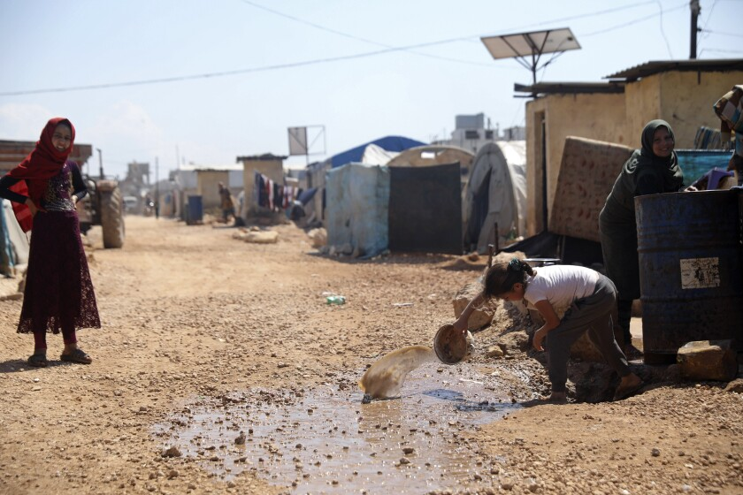 Refugees are shown at a large camp on the Syrian side of the border with Turkey in April.