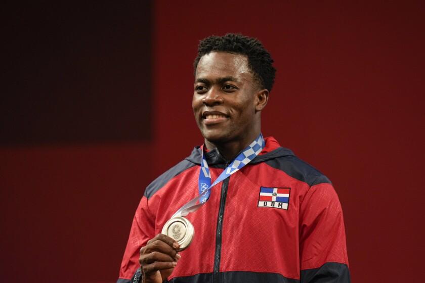 El dominicano Zacarías Bonnat exhibe su medalla de plata que ganó en la categoría de 81kg del levantamiento de pesas de los Juegos Olímpicos de Tokio, el sábado 31 de julio de 2021. (AP Foto/Luca Bruno)