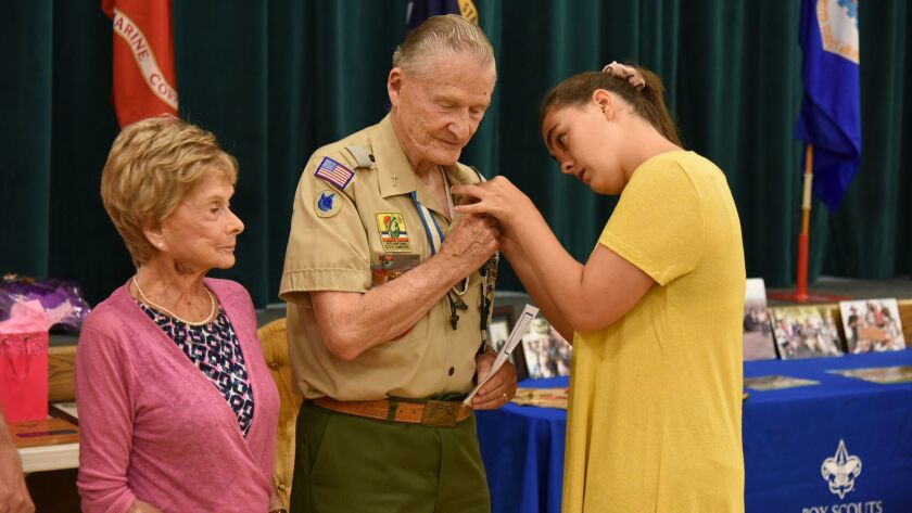 Ellie Preece, right of Vista, pins the Boy Scouts of America's 75-year Scout Veteran award on her grandfather, Richard Preece of Vista, as his wife, Nedra, looks on at a ceremony in his honor Thursday in Vista.