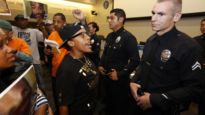 Protesters chant during an L.A. Police Commission meeting on Tuesday. The meeting, held on the first anniversary of the shooting death of South L.A. resident Ezell Ford, had to be halted briefly.