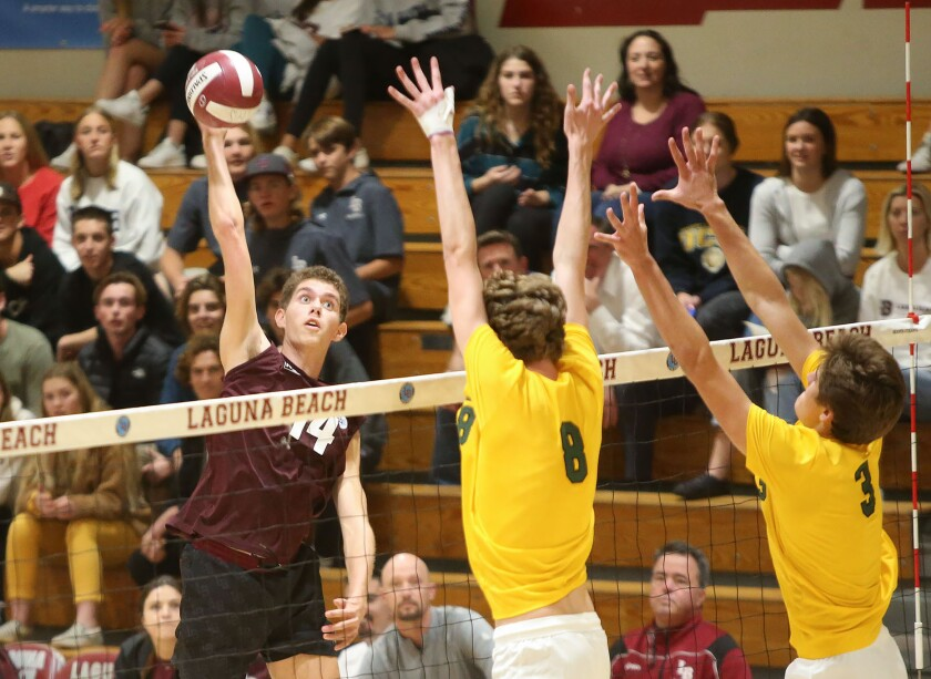 Laguna Beach outside hitter Andrew Reavis records a kill against Mira Costa blockers Dain Johnson (8) and Jack Walmer (3) during a nonleague match at home Wednesday.