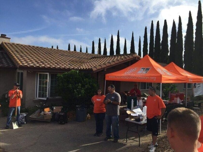 Volunteers from Home Depot helping Aquino build an outdoor patio to do woodworking.