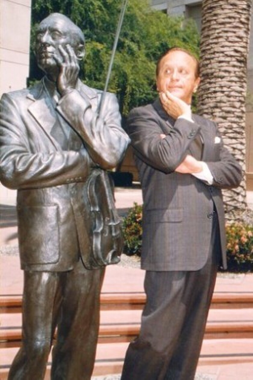 Eddie Carroll, who voiced Jiminy Cricket for Disney, poses with a statue of comic Jack Benny.