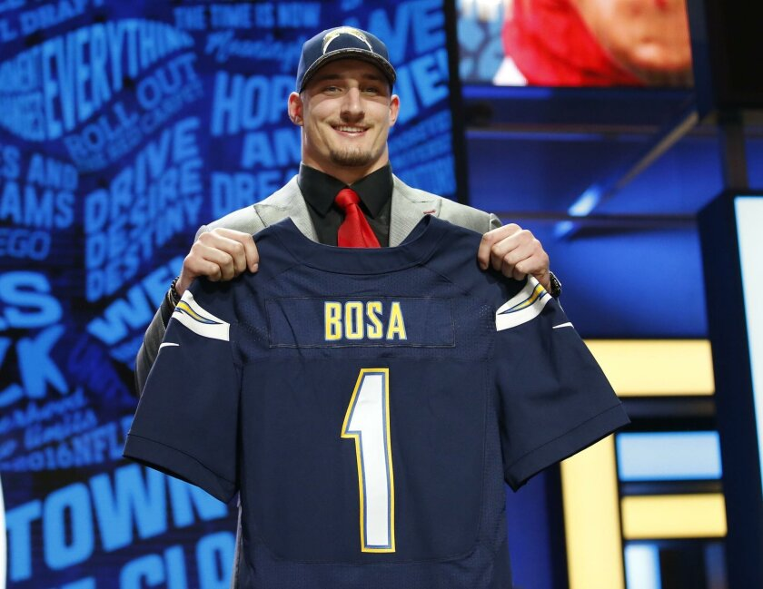 Joey Bosa poses with a Chargers jersey after the Chargers made him the third overall pick in April's draft.