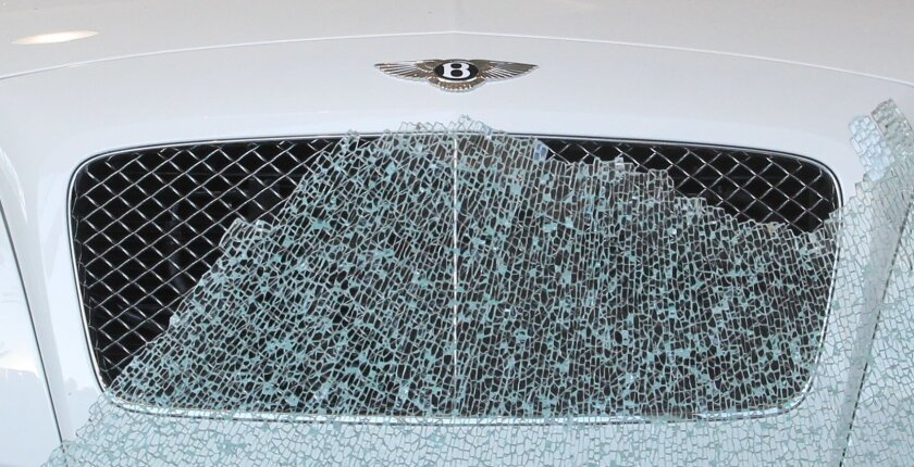 Thieves broke in to the Symbolic Motor Car Company business in La Jolla early Monday morning and stole four valuable Breitling watches from a glass showcase before fleeing.  Broken glass from the front door contrasted with the symetry of the Bently's front grill.