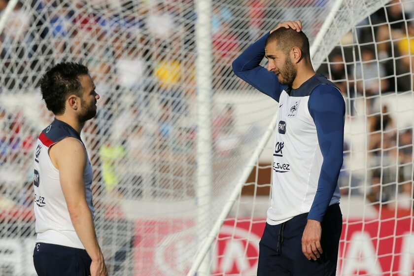 FILE - In this June 10, 2014 file photo, France's Mathieu Valbuena, left, and Karim Benzema, right, chat during a training session of the french national soccer team, at the Santa Cruz Stadium in Ribeirao Preto, Brazil. Benzema has been arrested Wednesday Nov.4, 2015 as part of an investigation int
