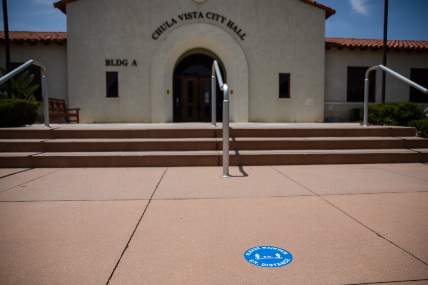 Signs reminding people to socially distance are seen all around Chula Vista City Hall on Wednesday, May 19, 2021.