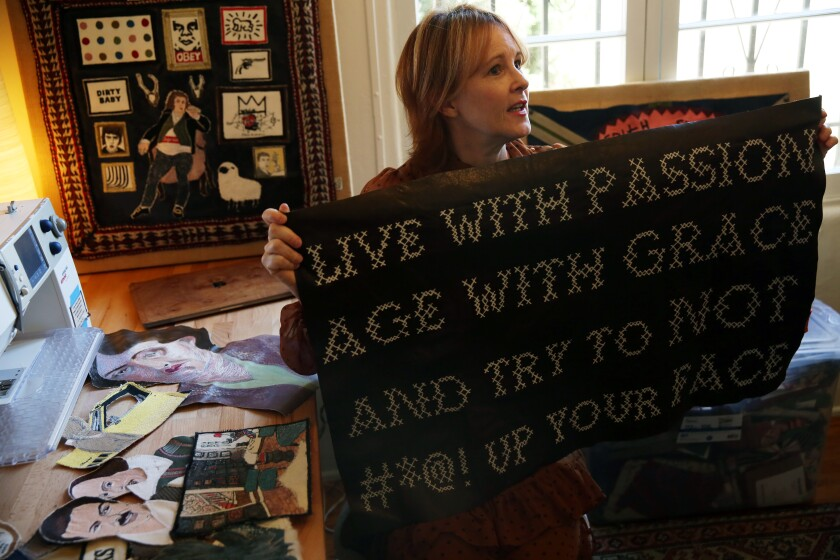 Lisa Borgnes-Giramonti holds up one of her embroidery pieces while in her home studio in Hollywood Heights