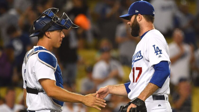 Dodgers catcher Austin Barnes, left, shakes hands with pitcher Brandon Morrow after earning a save in the ninth inning against the Angels at Dodger Stadium on June 27.