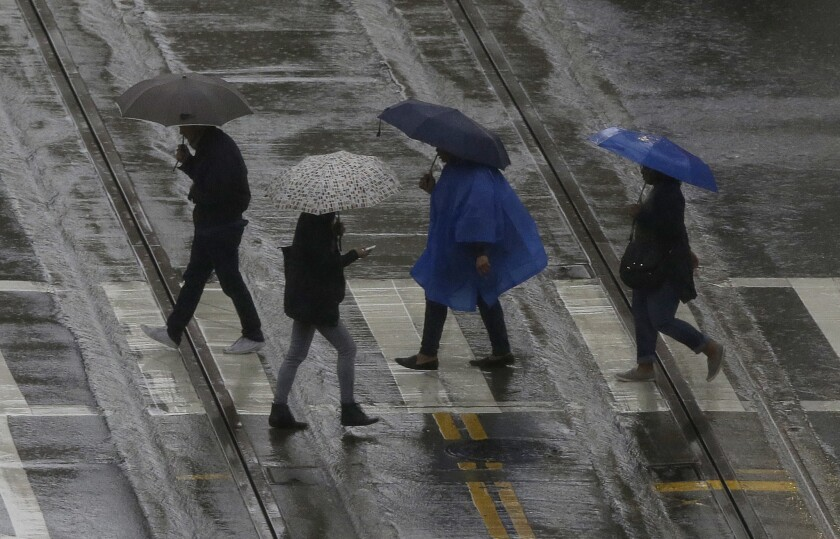 Pedestrians cross the street Friday in San Francisco. Storms brought rain and snow across California this weekend, and Southern California is dealing with another round of storms early Monday.
